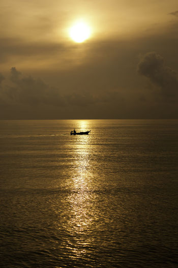 fisherman boat under the sunset Earth Beauty In Nature Cloud - Sky Day Fisherman Boat Goldenlight Horizon Over Water Idyllic Nature Nautical Vessel Outdoors Reflection Rippled Sailing Scenics Sea Sky Sun Sunlight Sunset Tranquil Scene Tranquility Twilightscapes Water Waterfront
