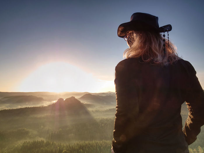 Fit body blond hair woman on top of high rocky mountain in evening. beautiful sunset autumn forest