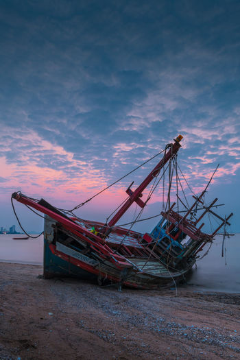 Ship moored on beach against sky during sunset