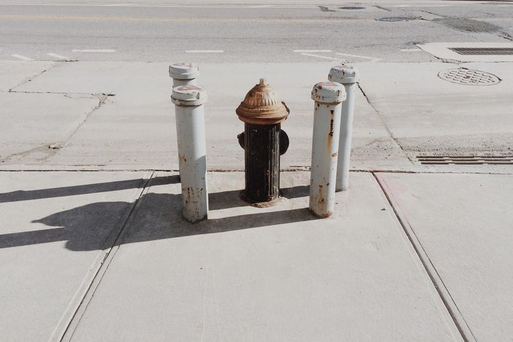 High Angle View Of Fire Hydrant Amidst Rusty Metallic Bollards On Sidewalk