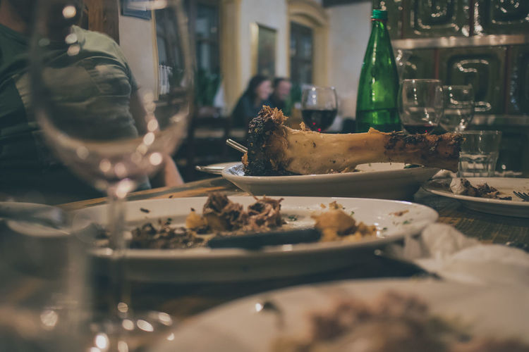 Midsection of man with leftovers on table in restaurant