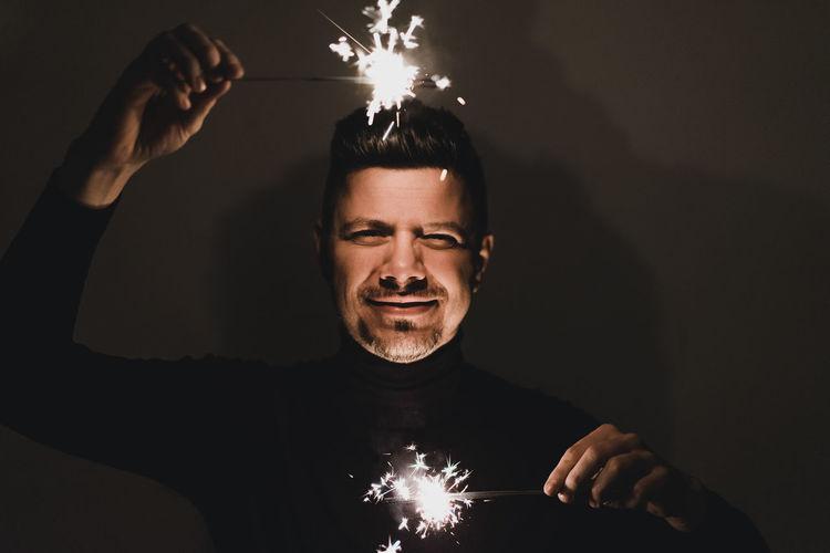 Close-up of man holding burning sparklers