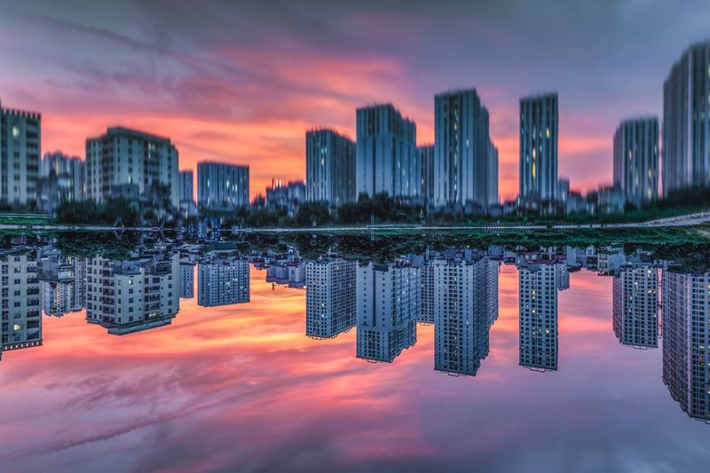 Modern buildings reflecting in river against sky during sunset