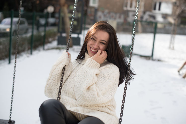 Portrait of happy young woman swinging in snow covered playground