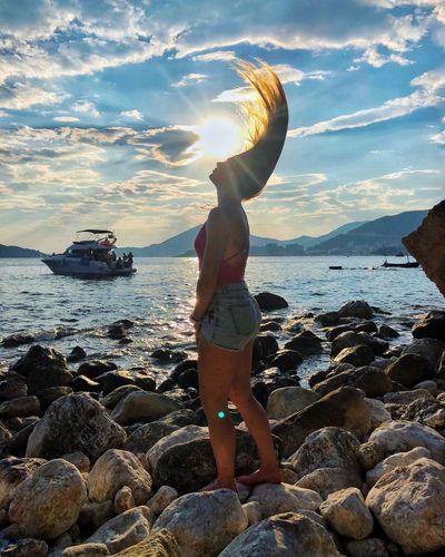 Man standing on rock in sea against sky