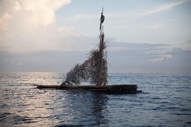 Drift wood floating on sea against cloudy sky