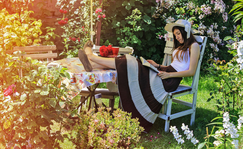 Adult Book Chair Day Domestic Life Flower Front Or Back Yard Full Length Happiness Lifestyles Nature One Person One Woman Only One Young Woman Only Outdoors Patio People Plant Relaxation Sitting Smiling Springtime Summer Women Young Adult