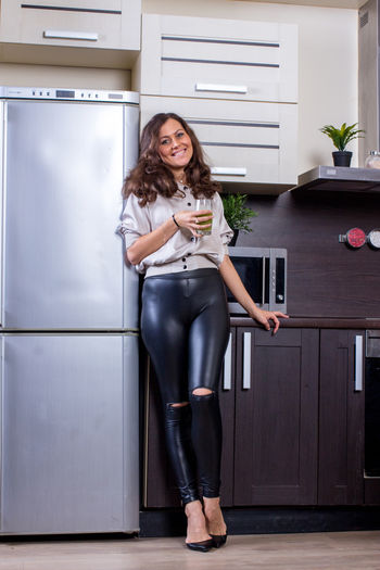 Full length portrait of smiling young woman holding food at home