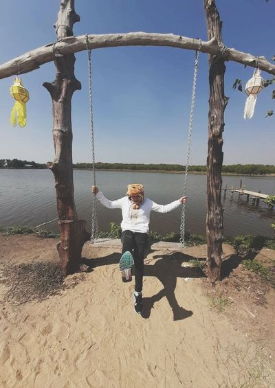 Woman standing on swing at playground