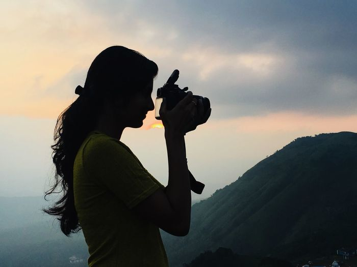 Side View Of Woman Photographing Mountains