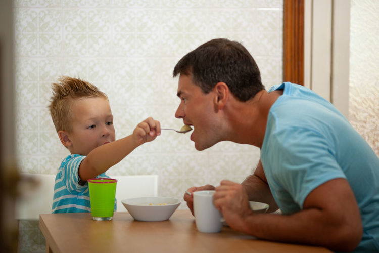 Cute son feeding food to father at home