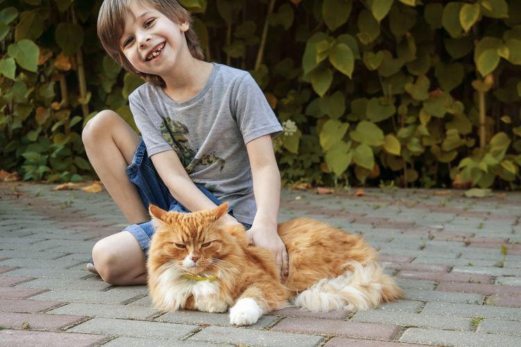 Full length of cat on boy