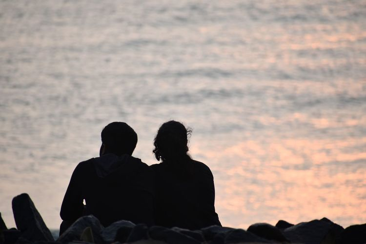 Rear view of silhouette couple sitting against sky during sunset