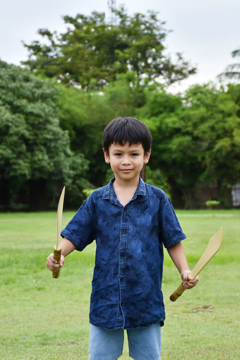 Boy holding wooden equipment while standing outdoors