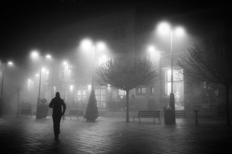 Man walking on illuminated street light at night