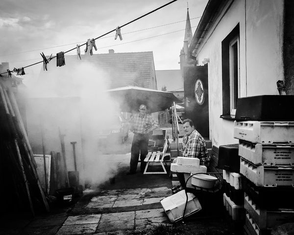 Blackandwhite Day Fish Fishing Village Heat - Temperature Occupation One Person Outdoors People Protective Workwear Real People Smoke - Physical Structure Smokehouse Working Fisherman Fisherman Village Black And White Kuźnica Miles Away