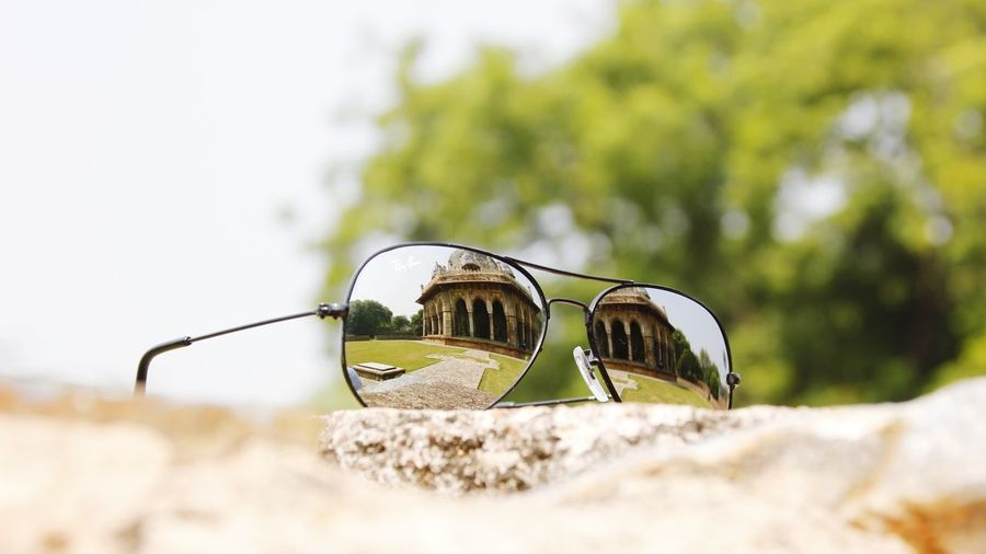 Close-up of sunglasses on retaining wall against sky