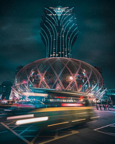 Illuminated ferris wheel in city at night