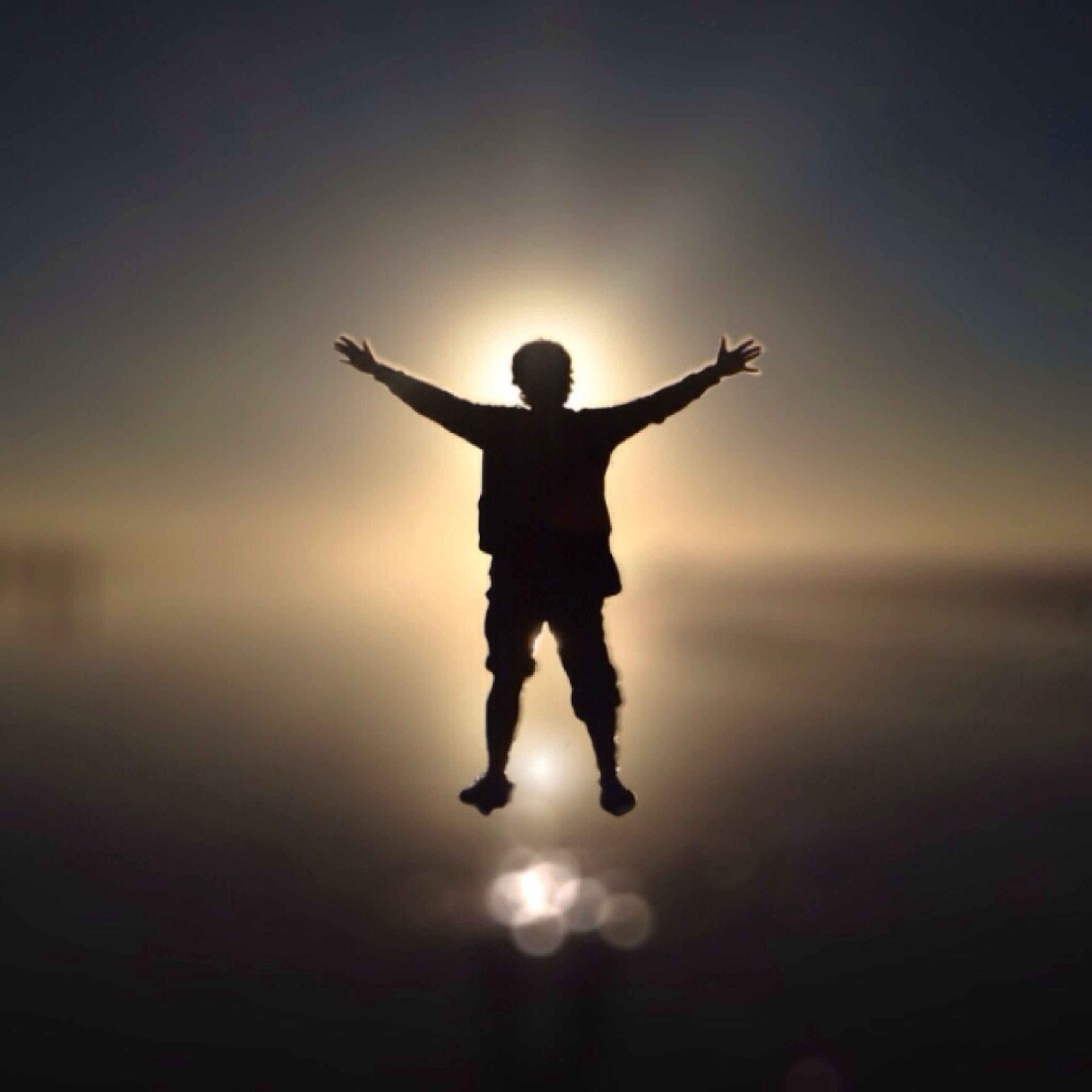 full length, sunset, lifestyles, standing, leisure activity, silhouette, sky, arms outstretched, childhood, water, sun, mid-air, arms raised, dusk, orange color, reflection, enjoyment, illuminated