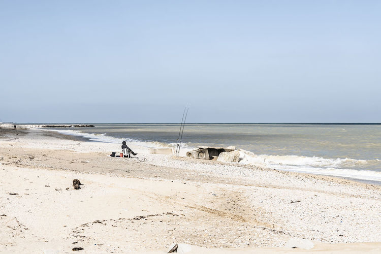 fisherman on the beach Fishing Equipment Fishing Pole Seascape Fishing Rods Food Environment Pollution Winter Solitude Absence One Person Leisure Activity Rock - Object Fisherman Adriatic Sea Coast Sand Cold Temperature Windy Day