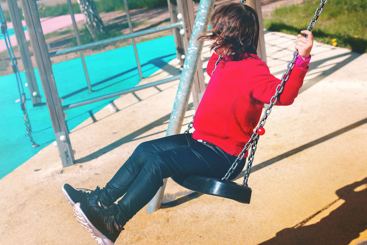 Woman sitting on swing in playground