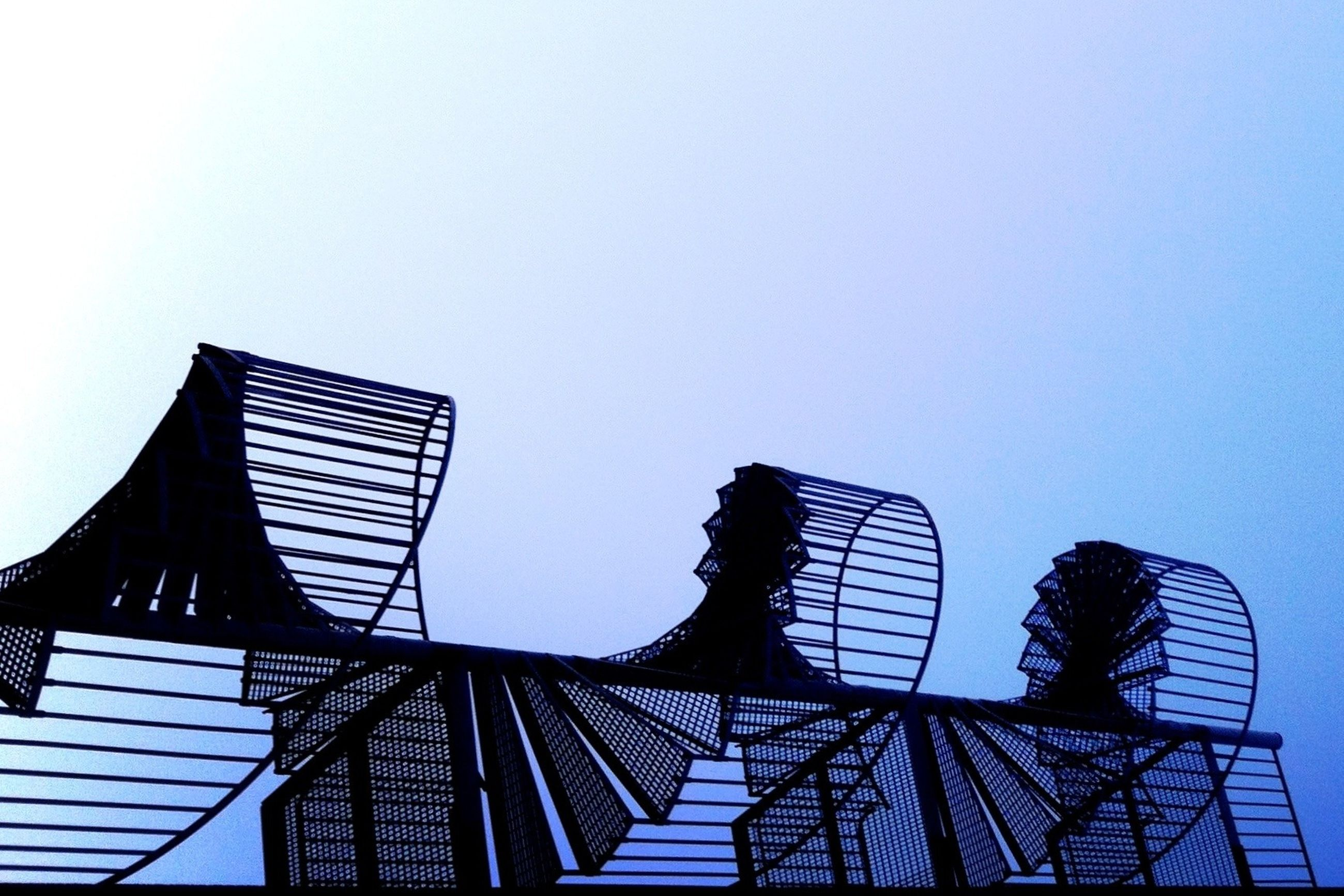 low angle view, clear sky, built structure, architecture, copy space, leisure activity, lifestyles, silhouette, men, sky, building exterior, standing, connection, arts culture and entertainment, railing, outdoors, person, rear view