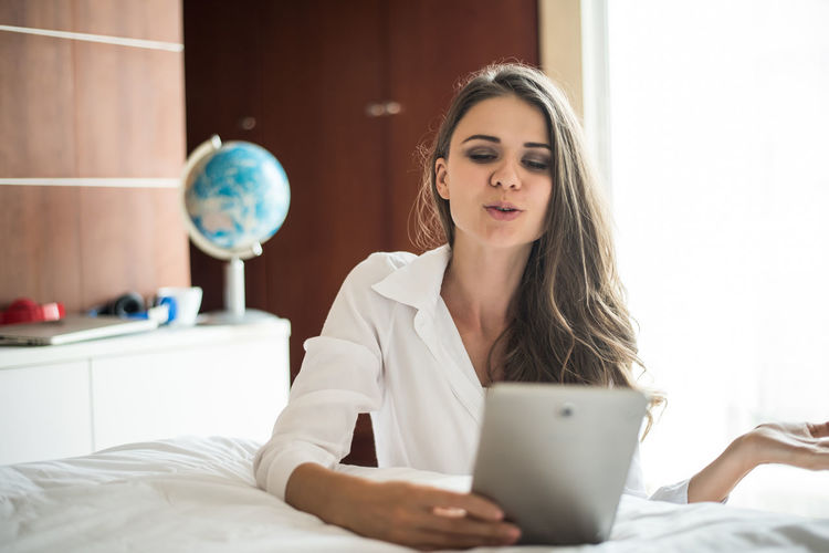Young Adult One Person Beauty Bed Women Indoors  Furniture Young Women Real People Adult Beautiful Woman Wireless Technology Front View Holding Communication Lifestyles Sitting Domestic Room Hair Using Laptop Hairstyle