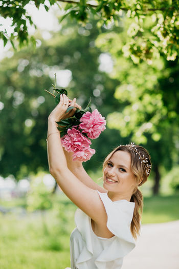 Portrait of young woman holding flower against plants