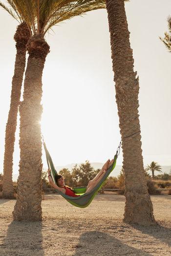 Full length of woman relaxing in hammock
