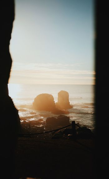 Beauty In Nature Copy Space Horizon Land Nature No People Orange Color Outdoors Rock Scenics - Nature Sea Silhouette Sky Sunlight Sunset Tranquil Scene Tranquility Water Window