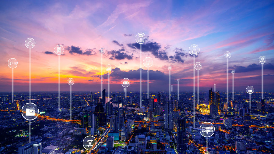 Digital composite image of illuminated buildings against sky during sunset