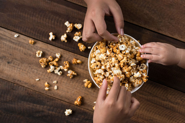 Cropped hands having popcorns in bowl on wooden table