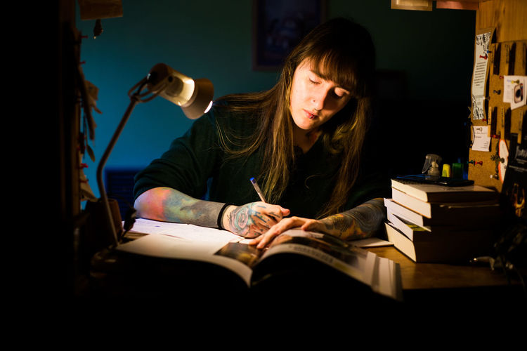 Young woman writing in book sitting at home