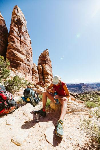Rear view of men on rock against sky