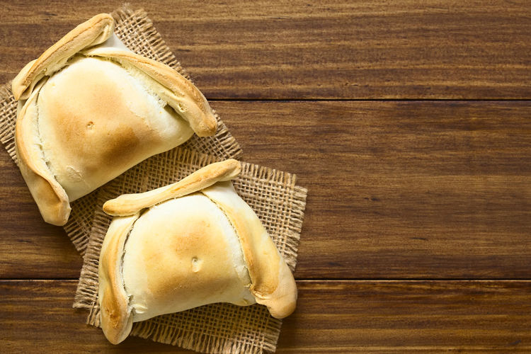 Chilean Empanada, a baked pastry stuffed with meat, photographed overhead on dark wood with natural light Beef Breakfast Chile Chilean  Empanadas Fast Food Filled Meal South American Food Stuffed Baked Bread Chilean Food Copy Space Empanada Empanada De Pino Food Food And Drink Meat Pastry Pasty Pino Savory Savory Food Snack