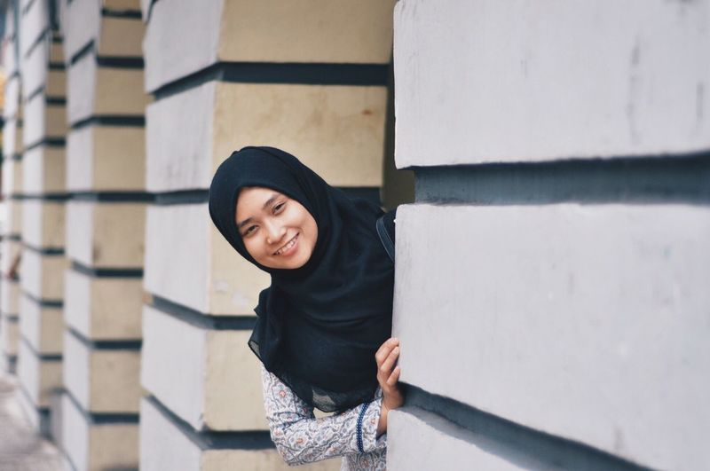 Portrait of smiling young woman standing by wall