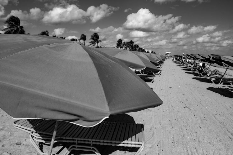 Shade Beach Beach Chairs Beach Life Beach Photography Beach Umbrella Blackandwhite Photography Cloud - Sky Day Focus On Foreground Fujifilm X-pro2 Fujifilm_xseries Landscape Large Group Of People Leisure Activity Nature Outdoors People Photographyisthemuse Sand Sky Summertime Sunny Day