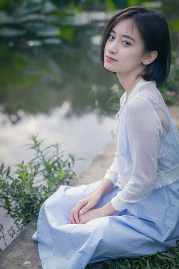 A beautiful young woman sitting besides the lotus. One Person Women Real People Lifestyles Leisure Activity Young Adult Sitting Young Women Casual Clothing Focus On Foreground Beauty Beautiful Woman Three Quarter Length Adult Hairstyle Day Plant Hair Bangs