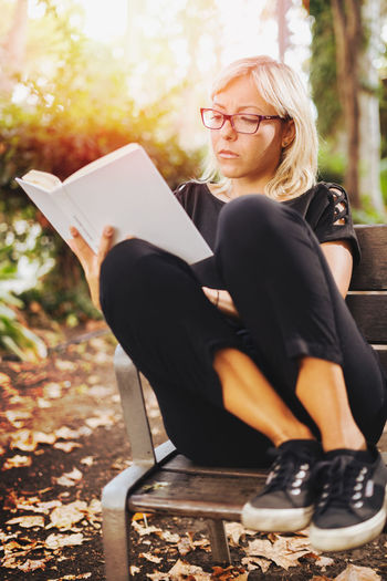 Young adult blonde girl reading a book outdoor in a park seat. Blank white book cover Autumn Activity Adult Beautiful Woman Blond Hair Book Casual Clothing Contemplation Eyeglasses  Full Length Glasses Hair Hairstyle Holding Leaves Leisure Activity Lifestyles One Person Outdoors Publication Reading Real People Seat Sitting Young Adult