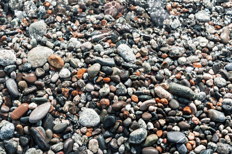 Pebble shore close up, natural background copy space, gray and red pebbles in sea water, texture