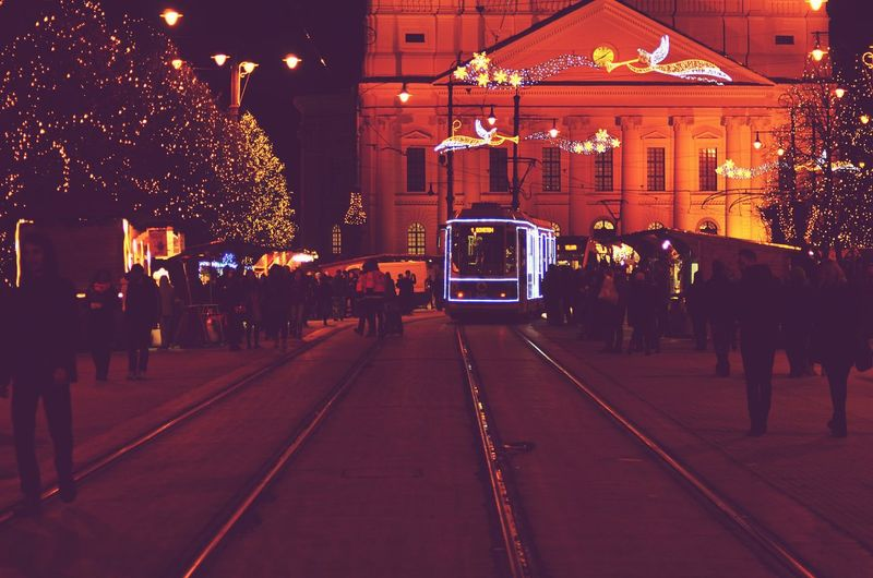 Illuminated Tramway Moving On Street Amidst People Against Decorated Buildings
