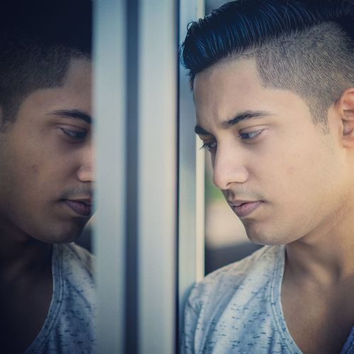 Close-up of thoughtful man reflecting in mirror