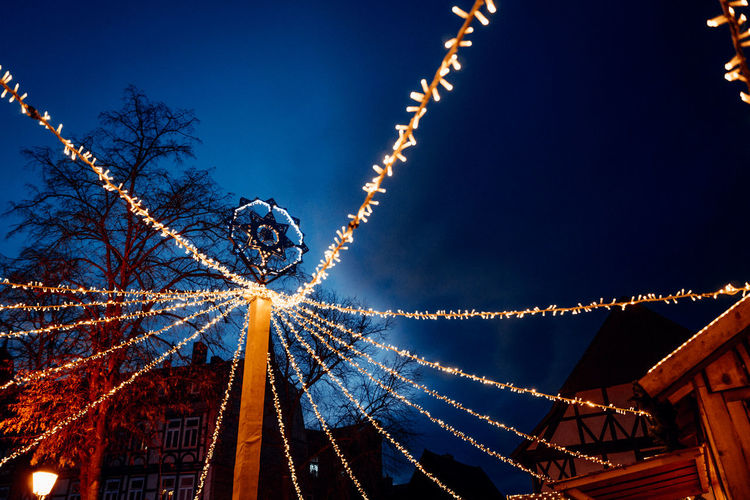 Low angle view of illuminated christmas lights against clear sky at night