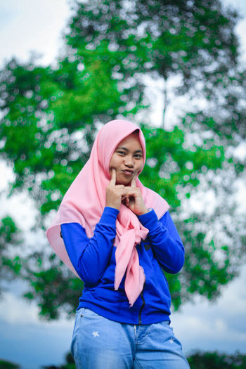 Portrait of young woman wearing hijab while standing against tree
