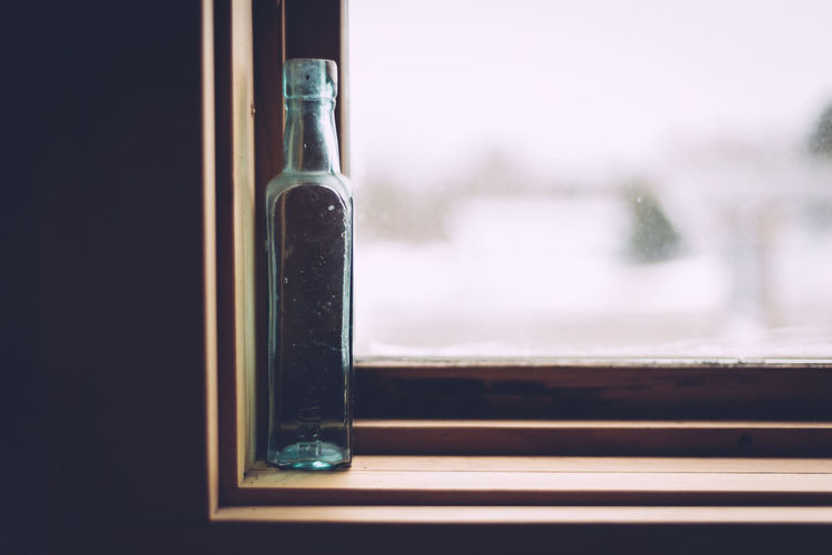 Close-up of glass bottle on window sill