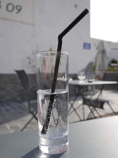 Close-Up Of Carbonated Water With Drinking Straw In Glass On Table