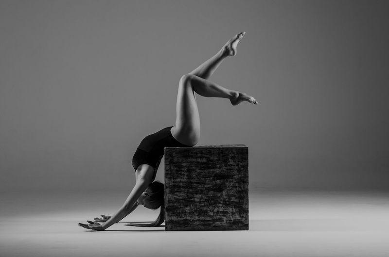 Full length of woman exercising against gray background