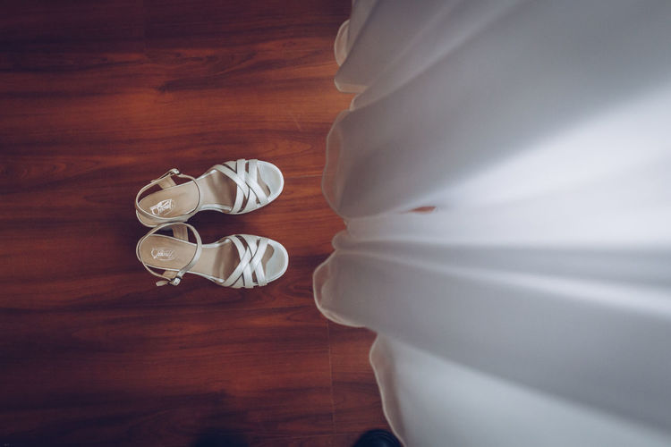 Low section of white shoes on wooden table