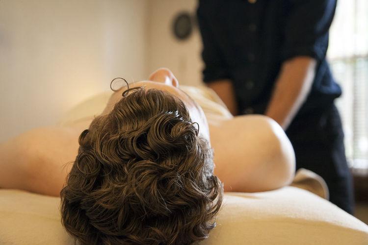 Massage therapist massaging man at spa