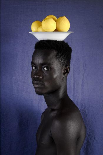Portrait of shirtless man against violet background